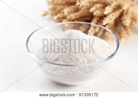 Glass bowl with flour and ears isolated on white