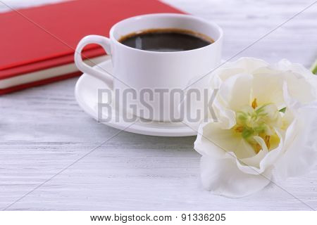 Fresh tulip, diary and cup of coffee on wooden table, closeup