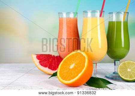 Fresh summer cocktails on wooden table on bright blurred background