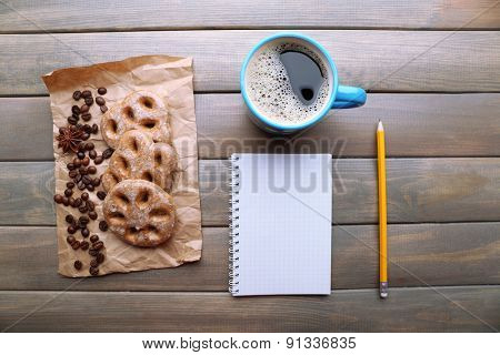Cup of coffee with fresh cookies and blank sheet of paper on wooden table, top view