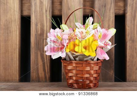 Beautiful flowers in vase on wooden background