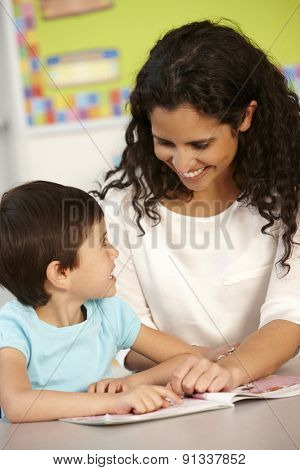 Elementary Age Schoolgirl Reading Book In Class With Teacher