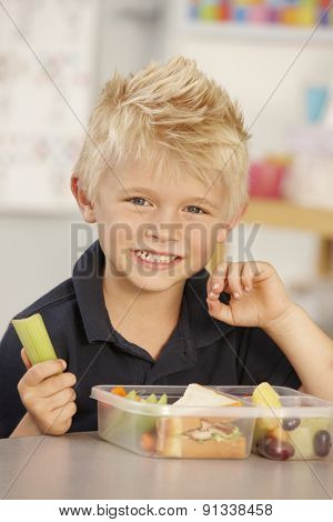 Elementary Age Schoolboy Eating Healthy Packed Lunch In Class
