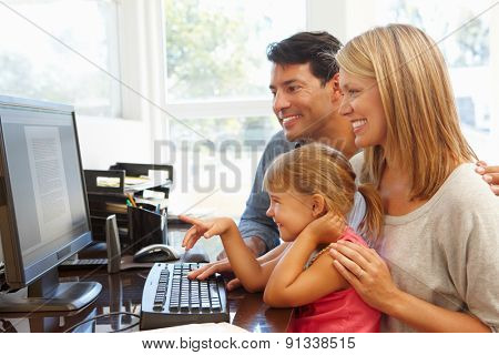 Couple working in home office with daughter