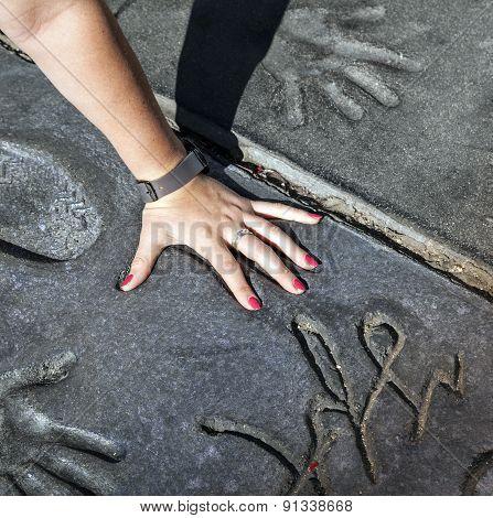 Fan Puts Hand In Handprints Of Twilight Saga Stars