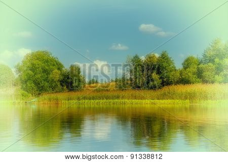 Summer landscape lake with reflection of trees in water.