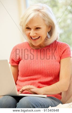 Mid age woman using laptop at home
