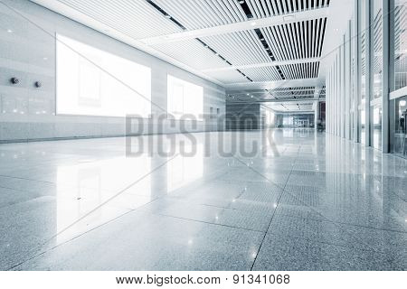 empty billboard and floor in shopping mall corridor