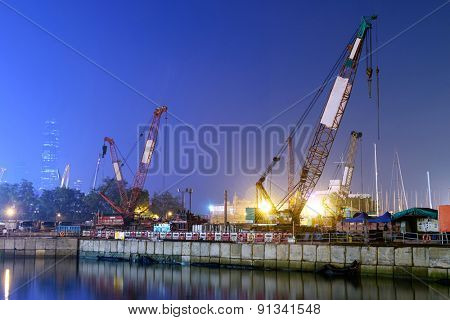 construction site and cranes near pond