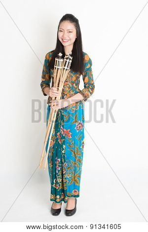 Full body portrait of Southeast Asian girl in batik dress hands holding pelita standing on plain background.