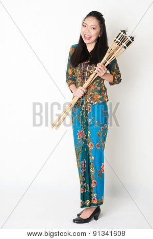 Full body portrait of Southeast Asian girl in batik dress hands holding bamboo torch standing on plain background.