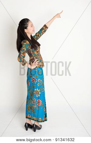 Full body side view of happy Southeast Asian woman in batik dress finger pointing away, standing on plain background.