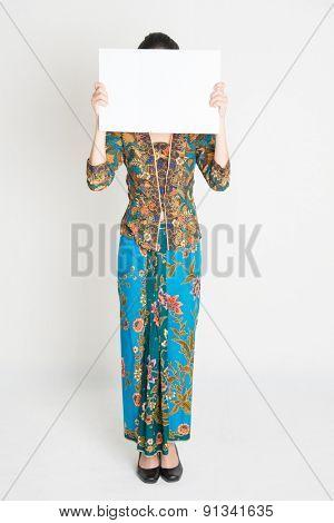 Full length Southeast Asian girl in batik dress holding a white card covering face standing on plain background.