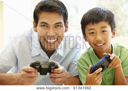 Asian father and son playing videogames