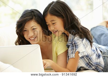 Asian mother and daughter using laptop at home