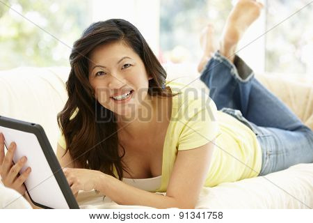 Asian woman using tablet at home