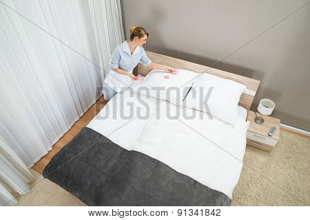 Maid Decorating Bedroom With Petals
