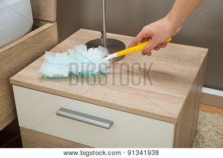Close-up Of Hand Removing Dust With Duster Feather