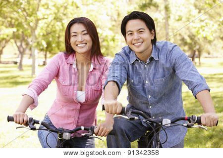 Asian couple riding bikes in park