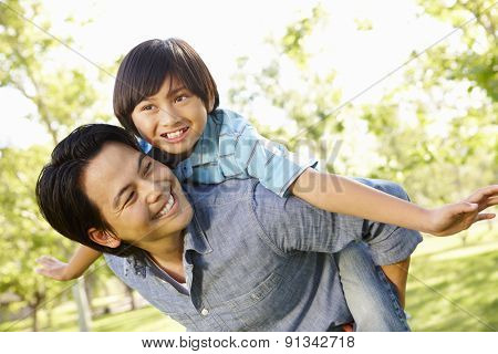 Portrait Asian father and son playing in park