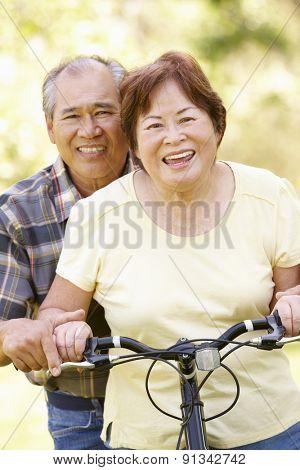 Senior Asian couple both sitting on one bike in park