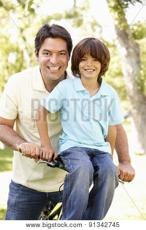 Young Hispanic Father And Son Cycling In Park