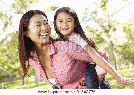 Portrait Asian mother and daughter playing in park