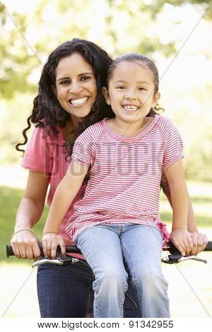 Young Hispanic Mother And Daughter Cycling In Park