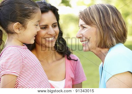 Hispanic Grandmother, Mother And Daughter Relaxing In Park