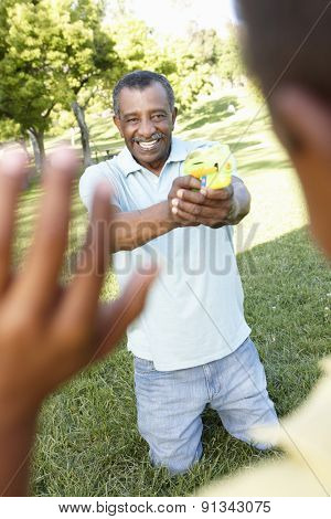 African American Grandfather And Grandson Playing With Water Pistols In Park