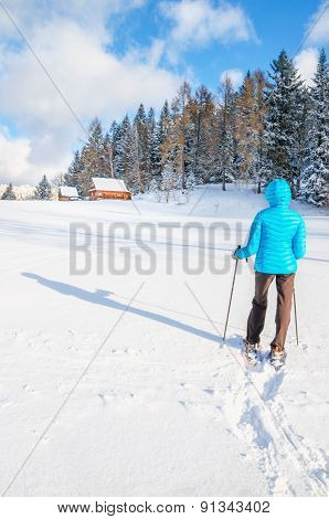 Young woman walking with snowshoes on fresh snow