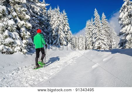Athletic man with snow shoes on winter trail