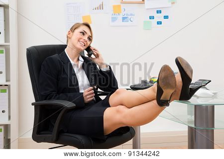 Businesswoman On The Phone With Feet On Desk
