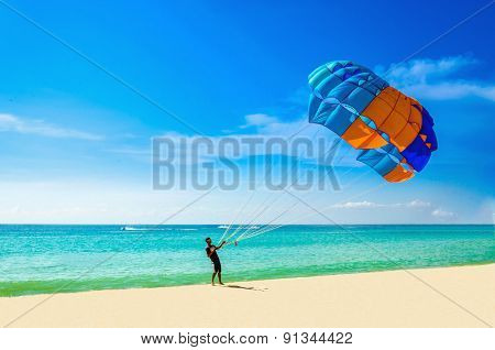 Thai man taking off parasail on beach, Thailand