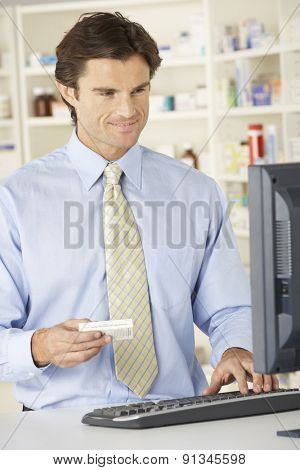 Pharmacist working on computer in pharmacy