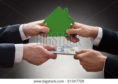 Businesspeople Holding House Model And Money