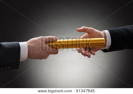 Two Hands Passing A Golden Relay Baton