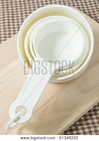 Four Plastic Measuring Cups On A Wooden Board