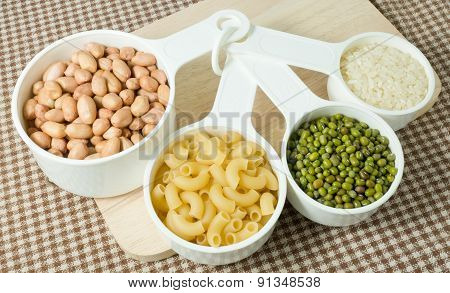 Pasta, Rice, Peanuts And Mung Beans In Measuring Spoons