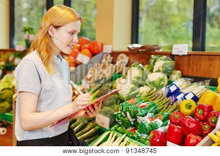 Woman in supermarket with clipboard making apprenticeship to become salesperson