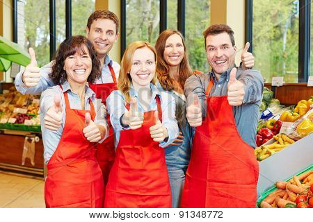Happy staff team in a supermarket holding their thumbs up