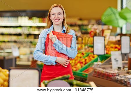 Smiling young saleswoman standing in supermarket with a checklist