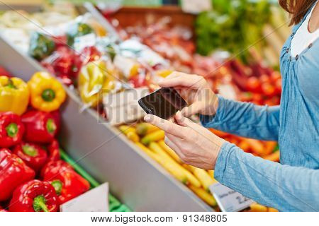 Woman comparing information of vegetables with her smartphone in a supermarket