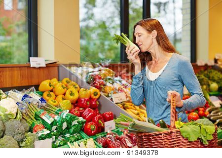 Woman smelling fresh fennel while shopping in a supermarket