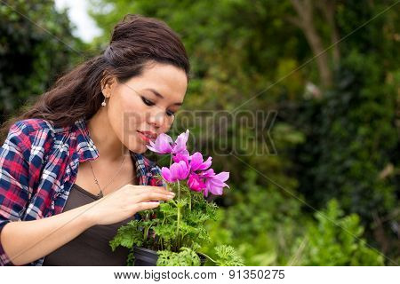 young woman smelling a flower in her garden