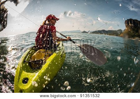 Young lady paddling the kayak in the sea with lots of splash