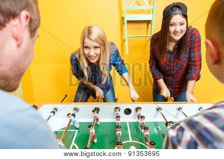 Happy friends playing table hockey