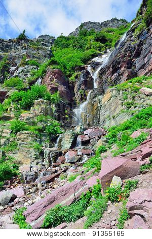 Waterfall And High Alpine Landscape Of The Grinnell Glacier Trail In Glacier National Park, Montana