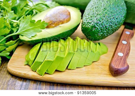 Avocado slices on board with knife