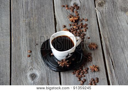 Coffee In A Coffee Cup In An Environment Of Coffee Grains And Anise Asterisks On A Wooden Table